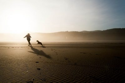 girl running with dog across a beach