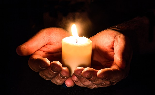 candle being held by a pair of hands