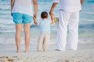 family standing together on a beach holding hands