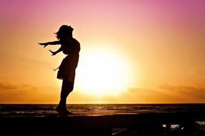 silhouette of woman standing with arms wide