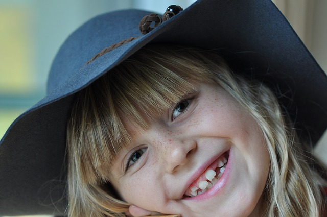 girl laughing with a hat on
