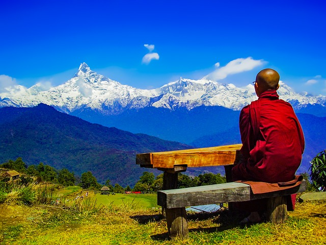 man sitting on bench above mountains