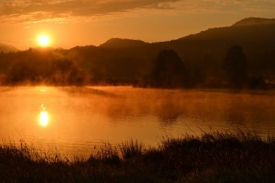 sunrise over a hill, infront of a lake