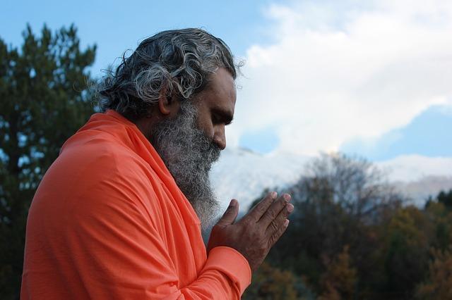 man wearing a orange sweater, praying