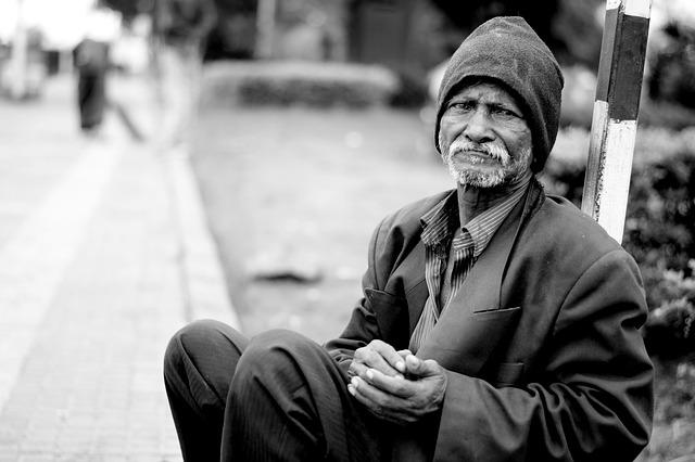man with scruffy beard sitting on road-side