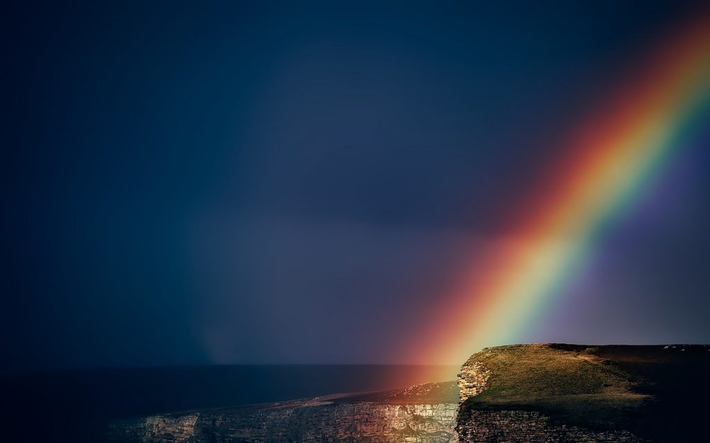 a rainbow over the coast of water