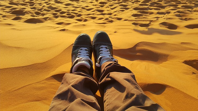 pair of feet sitting in the sand of a desert
