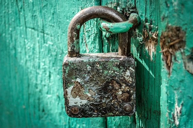 Rusted lock sitting on a blue-green door