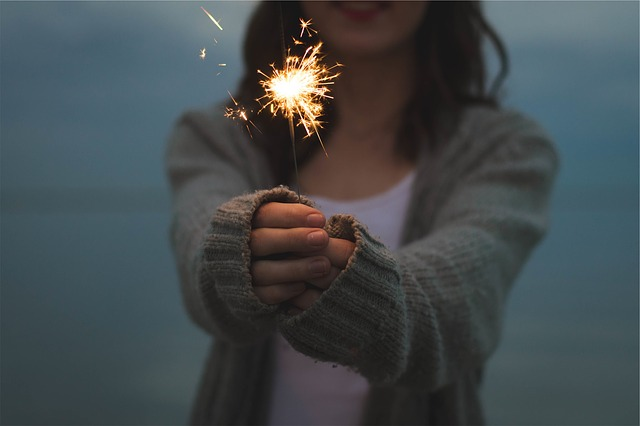 girl holding a lit sparkler