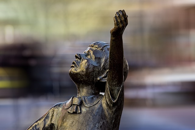 statue of a boy holding up his hand