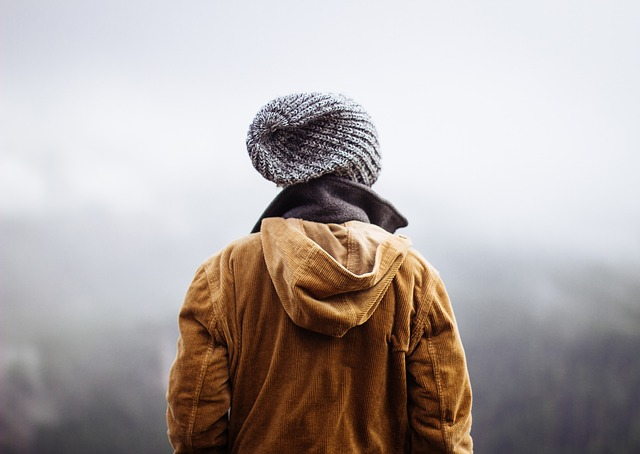 man standing in fog wearing a touque